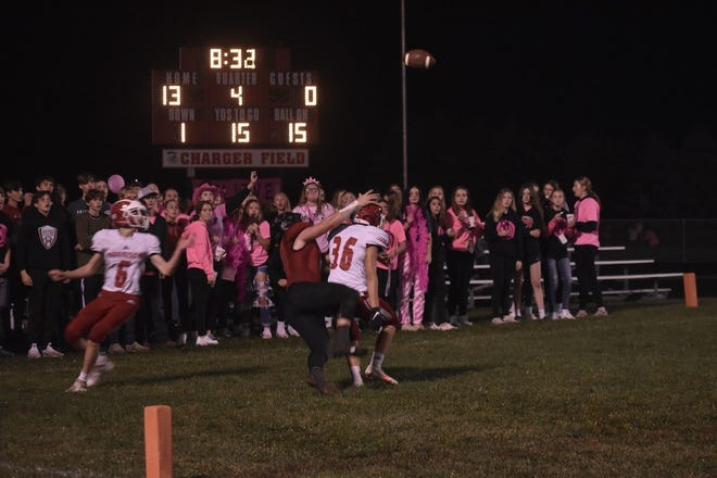 During Tackle Cancer Night on Friday, Oct. 8, the Orion students watch a pass float over a Charger receiver (red jersey) and a Morrison Mustang defender (white jersey)