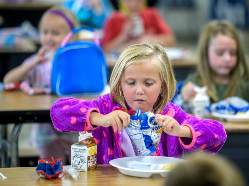 Sinclair Hopper, 6, opens a bag of mini-pancakes during lunch at Limestone Walters Elementary School in Bartonville.