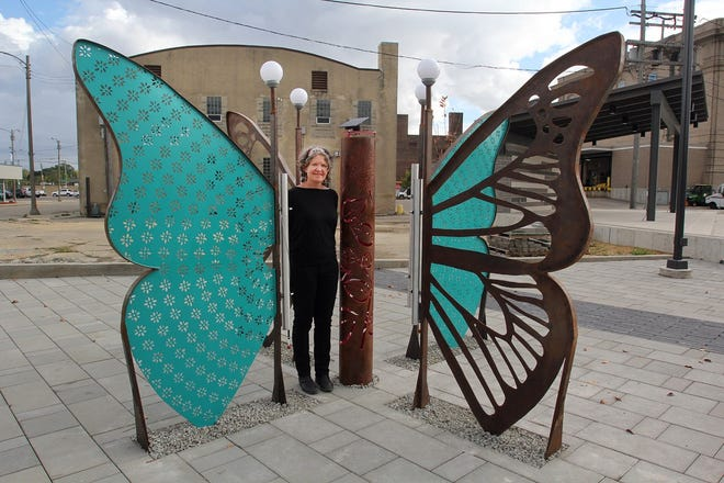 """Maureen Hearty of Joes, Colorado, stands in the middle of her sculpture, """"Renew,"""" on Friday, Oct. 8, 2021, at the Arts Plaza in downtown Freeport."""