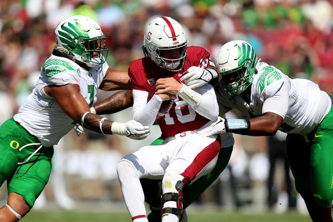 Oregon's Noah Sewell, left, and Brandon Dorlus, right, tackle Stanford quarterback Tanner McKee during their Oct. 2 game in Stanford, Calif.