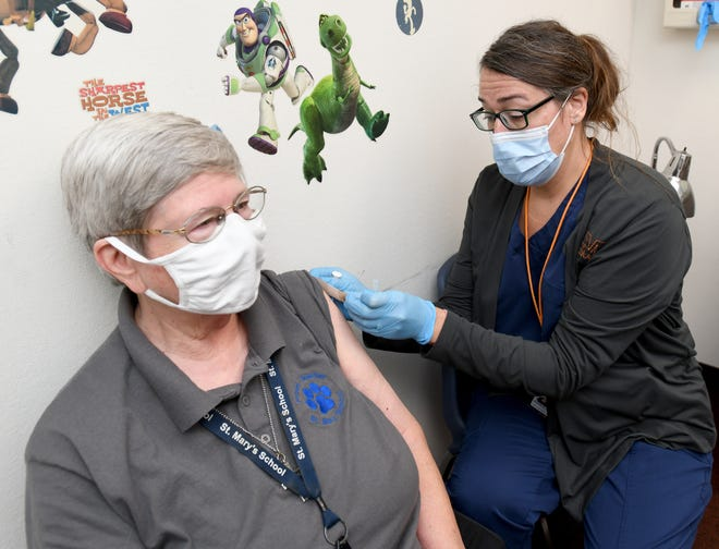 Sister Kathy Longheier with St. Mary's School receives a booster shot Tuesday morning from registered nurse Christine Gogerty during a COVID-19 vaccine booster clinic at Massillon Health Department.