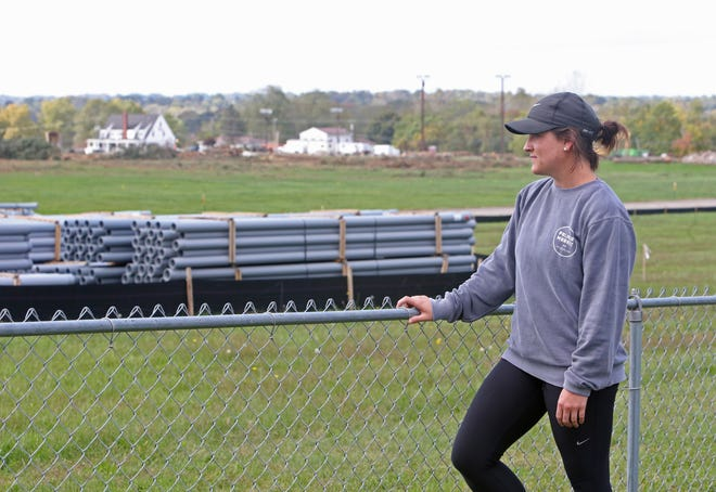 Sarah Morrison stands at her back fence as she speaks Tuesday about Amazon building a new warehouse at the former site of Skyland Pines Golf Club. Her backyard abuts the new Amazon property. Visible is conduit that will be used for lighting the property.