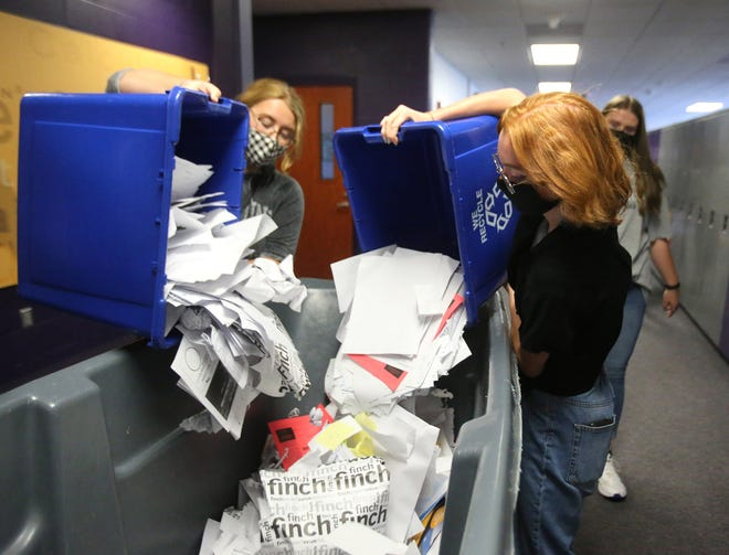 Kara Smith, left, and Fiona McCoury, right, of the Go Green Club dumps paper to be recycled into a bin Tuesday at Jackson High School.