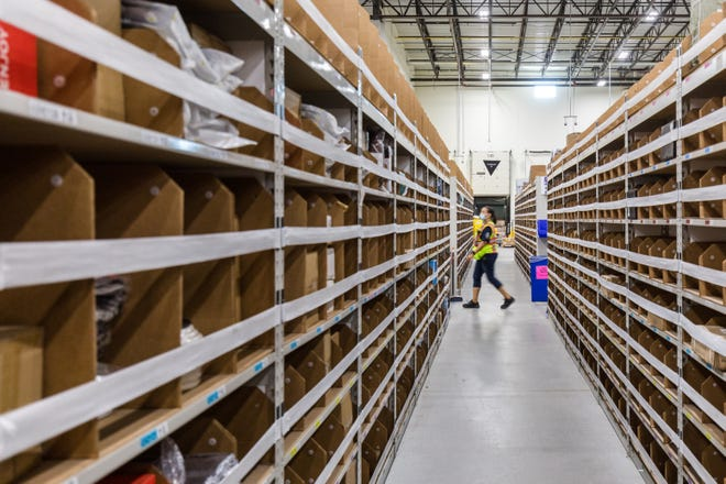 An employee walks among the shelves at an Amazon distribution center in the Detroit area. Amazon is building a fulfillment center in Canton on the former Skyland Pines Golf Club property.