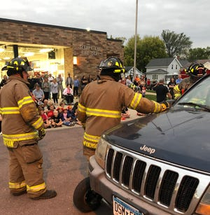 After enjoying supper inside the station, people at the Fire Department Open House on Oct. 6, came out front to watch firefighters demonstrate how they use extrication tools to get into vehicles when damaged doors cannot be opened.