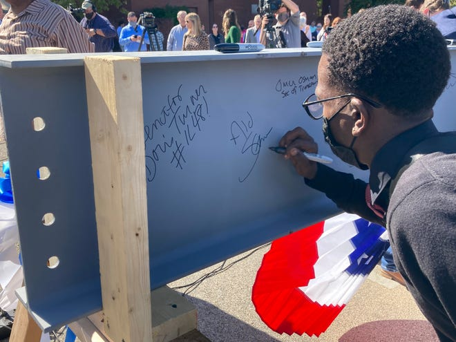 Springfield City Council Ward 2 Ald. Shawn Gregory signs a beam that will be used to during the construction of the Springfield-Sangamon Transportation Center during a groundbreaking ceremony Tuesday at 10th and Adams streets.