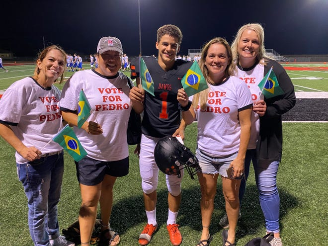"""Rossville parents make Pedro Arantes, center, feel at home on the football team by carrying Brazil flags and sporting """"Vote for Pedro"""" shirts to the games."""