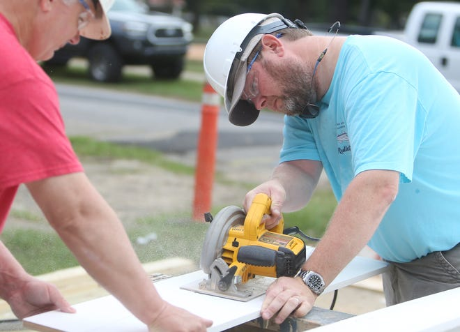 Brock Corder, president of The Builders Group, saws a piece of lumber with Claude Edwards, the president of Bryant Bank, at a Habitat for Humanity of Tuscaloosa construction site on Tuesday, Oct. 12, 2021. [Photo/Will McLelland]