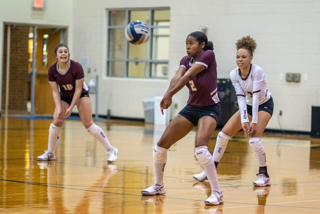 Red Oak's Makinzie Taplin (2) returns a serve as teammates Chloe Munoz (18) and Mizani McKellar (2) look on during Friday evening's match against Midlothian at Frank Seale Middle School.