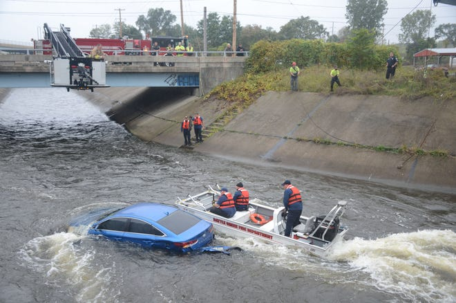 Battle Creek firefighters in a boat approach a car in the Kalamazoo River following a crash Tuesday.