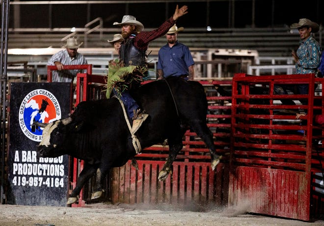 Ralph Hobson, of Junction City, tries to stay on the bull coming out of the paddocks during the A-Bar Rodeo held in front of a packed grandstand at the Fairfield County Fair in Lancaster, Ohio on October 11, 2021. To view more photos visit https://www.lancastereaglegazette.com