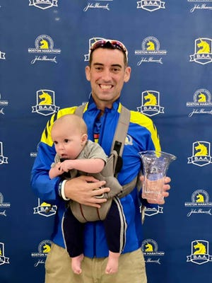 Louisville runner Joe Burket who is blind finished second at the 125th Boston Marathon in the vidual impairment division. He is pictured here after the race with his 7-month-old son Ryan.  Oct 11, 2021.