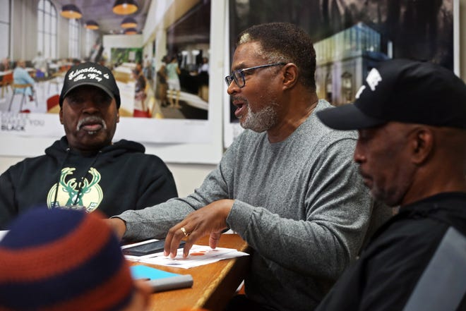 Earl Ingram Jr., center, discussed the struggles facing single mothers raising troubled sons during a meeting of a newly formed group, Voices of the Elders, on Thursday at Coffee Makes You Black. Ingram is part of a group of senior community leaders and advocates who hope to change the lives of troubled boys.