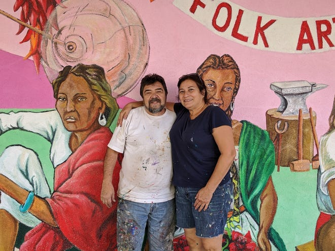 Carlos Callejo, left, and Blanca Aldana pose in front of a mural that both artists helped construct on Bullard Ave.