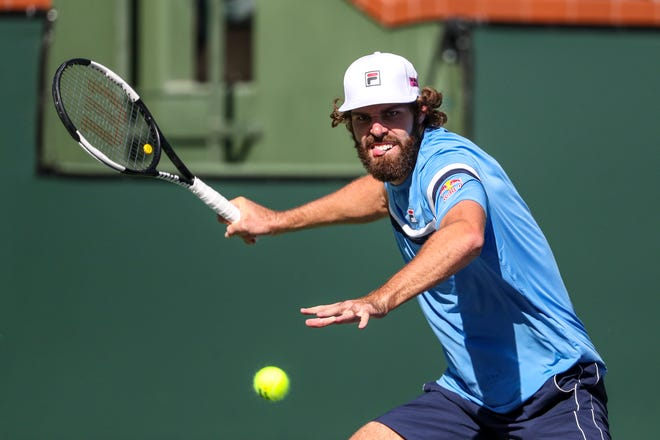 Reilly Opelka of the United States returns the ball to Grigor Dimitrov of Bulgaria during their round three match of the BNP Paribas Open, Monday, Oct. 11, 2021, in Indian Wells, Calif.