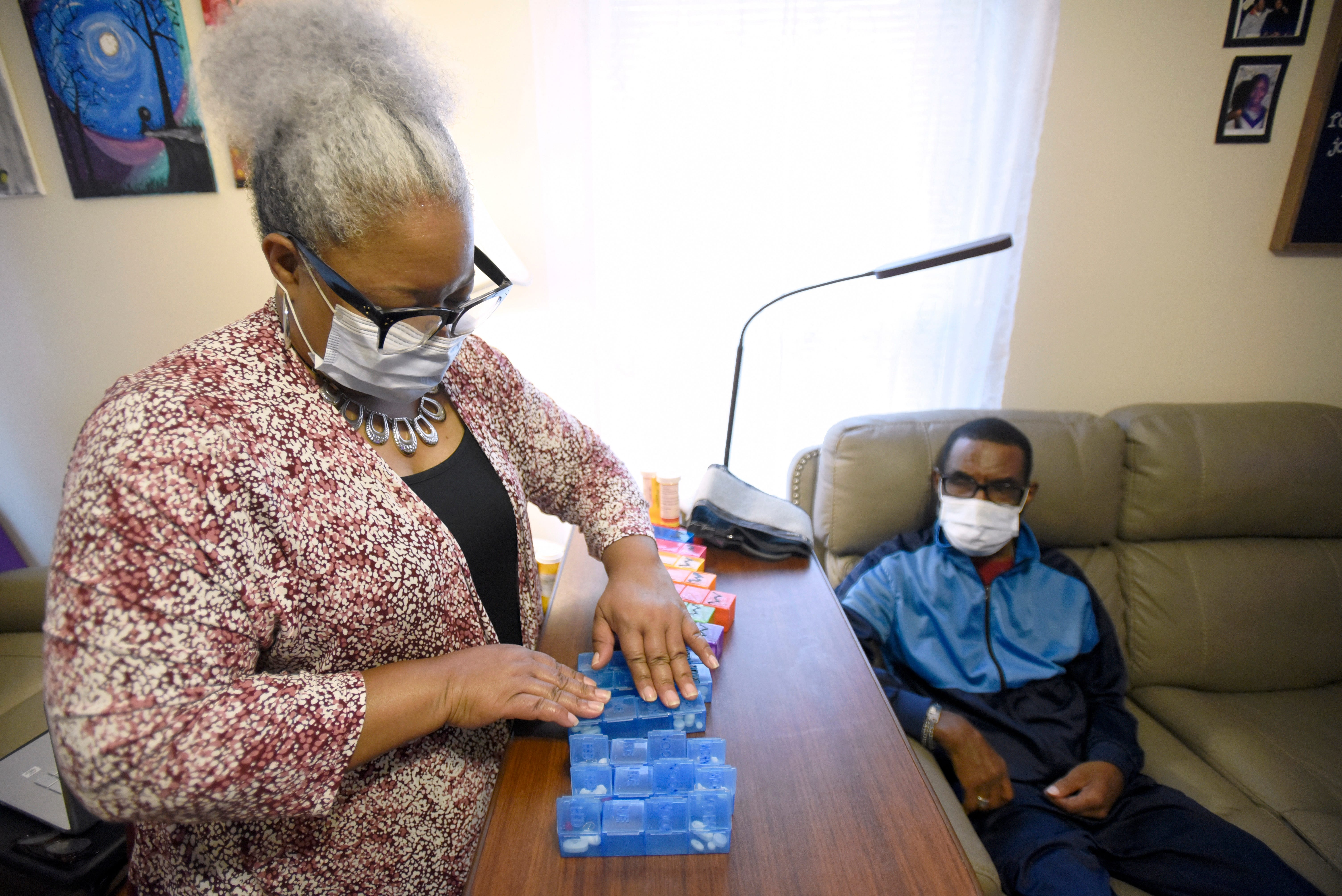 Theresa Robertson, left, 58, organizes medication for her husband, Emanuel, 63, at their home in Elkridge, Md., Sunday, Oct. 10, 2021. Photo by Steve Ruark