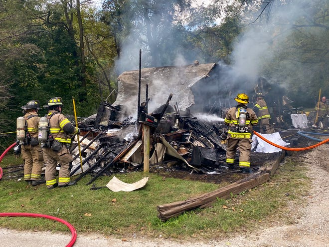 Firefighters keep flames from rekindling following a fire that destroyed a family's mobile home on Green Street Tuesday morning. Ten dogs were killed and a teenager was injured during the fire.