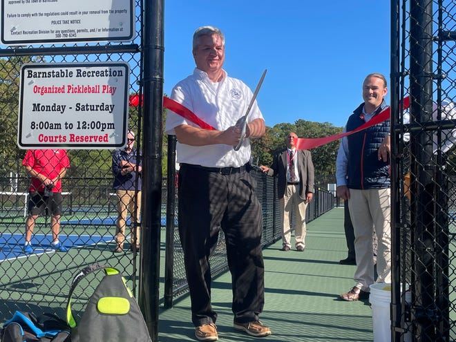 Barnstable Town Architect Mark Marinaccio does the honors of the official ribbon-cutting and dedication of 16 new pickleball courts next door to West Villages Elementary School.