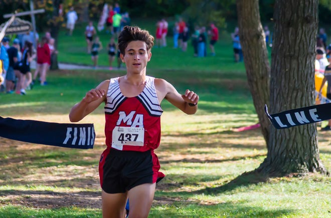 Moon Area's Jacob Puhalla crosses the finish line to win the MAC cross country championships Wednesday at Settlers Cabin Park. [Lucy Schaly/For BCT]