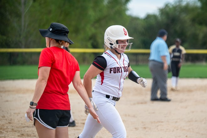 Fort Osage senior Savannah Short, right, slaps hands with coach Kelly Sullivan after slugging a three-run home run in the fourth inning of Tuesday's Class 5 District 7 opener against Lee's Summit. The blast gave the Indians a 4-1 lead but Lee's Summit rallied for a 7-5 victory.