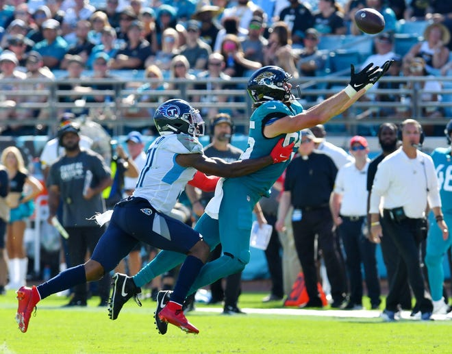 Tennessee Titans safety Kevin Byard (31) grabs Jacksonville Jaguars tight end Dan Arnold (85) as he stretches for an overthrown pass with just under four minutes to play in the fourth quarter. The Jacksonville Jaguars hosted the Tennessee Titans at TIAA Bank Field in Jacksonville, Florida, October 10, 2021.  The Jaguars trailed at the half 24 to 13 and lost with a final score of 37-19. [Bob Self/Florida Times-Union]