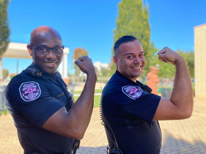 Officers Gregory Tucker, left, and Alvaro Jaines display the pink Breast Cancer Awareness patches on their uniforms.