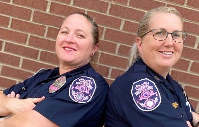 Officer Jackie Quinley, left, and Capt. Laura Biggerstaff display their pink Breast Cancer Awareness Month patches.