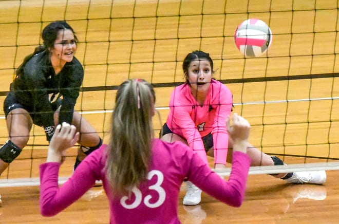 Garden City High School's Taylor Mesa, right, digs an Ulysses serve as Jesy Foster looks on during a volleyball match Oct. 7 at GCHS.