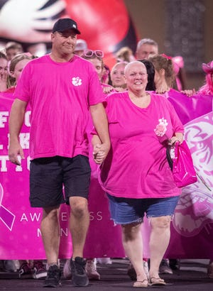 Melissa and Michael Young lead the Glen Rose Athletic Booster Club's Victory Lap of Life as part of Breast Cancer Awareness Month last Friday. Melissa is currently battling breast cancer. The one-lap walk around the track took place during halftime of Glen Rose's 41-24 victory over Godley. The walk was a show of support for all those battling breast cancer and a remembrance of those who have lost that battle. Fans purchased pink-out shirts and wore them at the game in honor of the event.