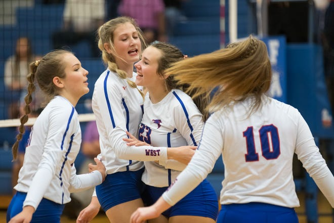 Carley Raleigh (23) celebrates a point with teammates Amber Huard (11), Payton Brown (10), and Emma Bryson (5) Tuesday night. [PAT SHRADER/ SPECIAL TO THE TIMES-NEWS]