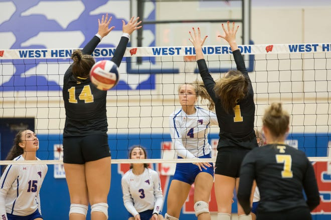 West Henderson's Caitlyn O'Kelly (4) spikes the ball between two Tuscola defenders Tuesday night in West Henderson's 3-1 victory at West.