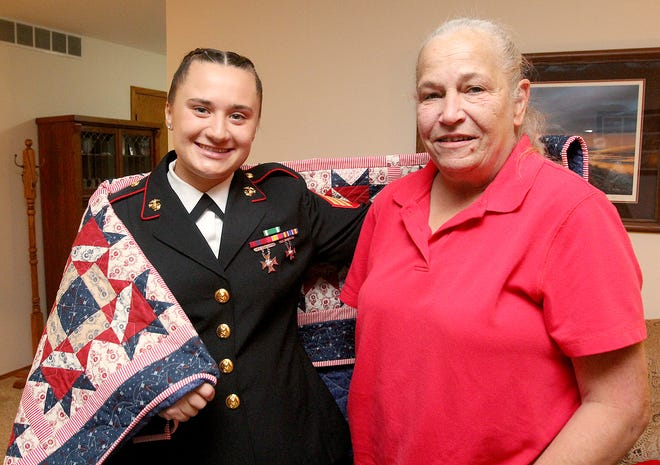 Libby DeWall, left, wraps herself in the Quilt of Valor presented to her by Nancy Smith on Thursday, Oct. 7, 2021, in Freeport. DeWall, a U.S. Marine, was given the quilt for her service, sacrifice and valor.