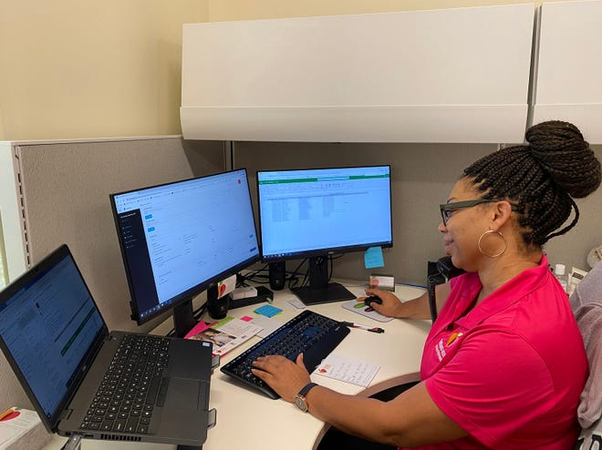 All Faiths Food Bank specialist Mia Pompey assists a community member. The All Faiths team has received extensive training to learn more about the Florida KidCare program.
