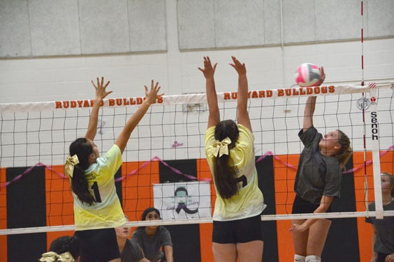 Pickford's Madison Thurmes attacks against Rudyard blockers Eve Cheney (11) and Meagan Postma (17) during the Volley for a Cure match Tuesday.