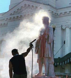 A city worker pressure-washes paint from the Christopher Columbus statue Wednesday in front of Union Station.