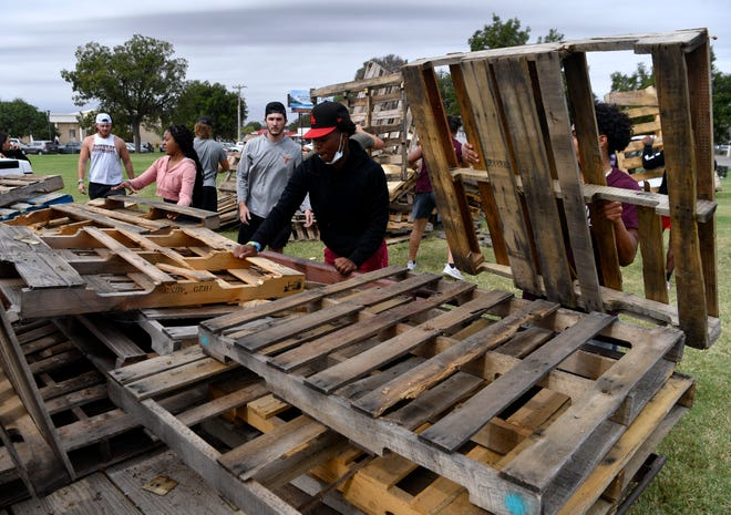 Students at McMurry University unload a trailer of pallets for this weekend's Homecoming bonfire on Wednesday before rain began falling in Abilene about mid-afternoon. Clear skies are forecast for local homecoming events that included those at Abilene Christian University.