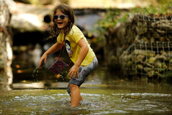 Willow Bender, 6, of Amelia, laughs as she slips and takes a dunk in the stream at the California Woods Nature Preserve in the California neighborhood of Cincinnati on Wednesday, Oct. 13, 2021. Fall colors have begun to emerge as the Cincinnati autumn temperatures still linger in the upper-70s.
