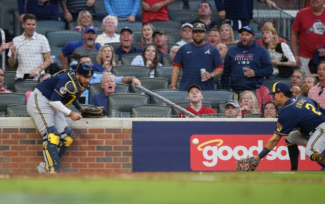 Milwaukee Brewers third baseman Luis Urias (2) catches a ball in foul territory that was deflected by catcher Omar Narvaez during the fourth inning the ball appeared to hit the ground.