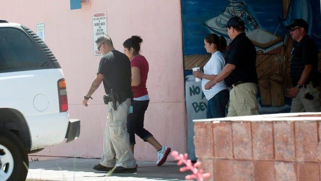 Fotografía de archivo en la que se observa a agentes del Servicio de Inmigración y Aduanas (ICE) llevar arrestadas a dos mujeres, presuntamente inmigrantes indocumentados durante una redada en Tucson, Arizona.