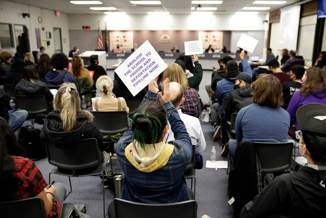 Audience members applaud and wave signs as a community member finishes testifying before the Salem-Keizer school board Tuesday evening.