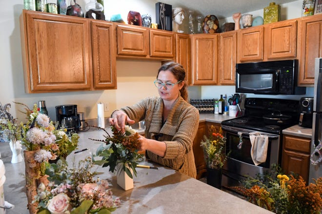 Statement vases line the cabinets in the kitchen as Jada Pyper, owner of The Vibrant Daisy, prepares a flower arrangement for the next day's delivery on Wednesday, October 13, 2021, at her home in Sioux Falls.