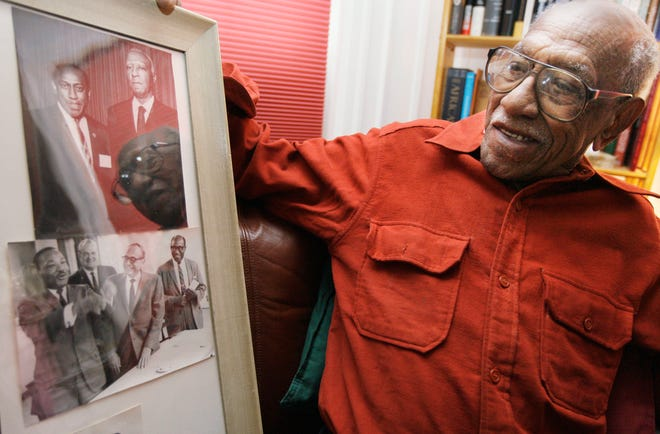 Timuel Black, 90, holds framed photos of himself, Dr. Martin Luther King Jr. bottom, and A. Phillip Randolph, top, in his days as a civil rights leader and political activist in his apartment Wednesday, Jan. 14, 2009 in Chicago.