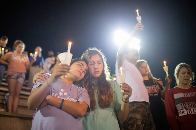 Lilly Yahya and Sarah White lean on each other during a vigil for Battle Creek Middle School sixth-grade student Kailee Grace Warren, 11, a victim of a shooting, at Spring Hill High School in Spring Hill, Tenn., on Wednesday, Oct. 13, 2021.