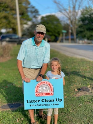 Community organizer Greg Martin and neighbor Macy Irvin place signs in residents' yards regarding a Litter Clean Up day on Saturday.