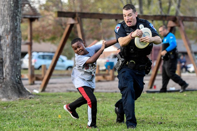 Mike Hicks, an officer with Blue Ridge Community College, is tagged by Mehki-lee Daughtry, 8, as they play a Frisbee game during National Night Out in Hendersonville Wednesday.