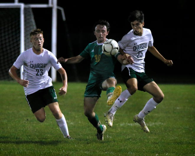 Chariho's Richard Lambert rushes in as Smithfield's Liam Hickey and Chariho's Christopher Niziolek battle for a bouncing ball during first half action as the Sentinels host the Chargers on Oct 14, 2021.