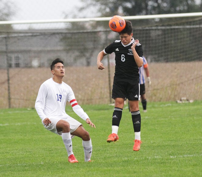 Christian Luna of Sturgis heads a ball back to a teammate to keep possession against Harper Creek in district soccer action on Wednesday.