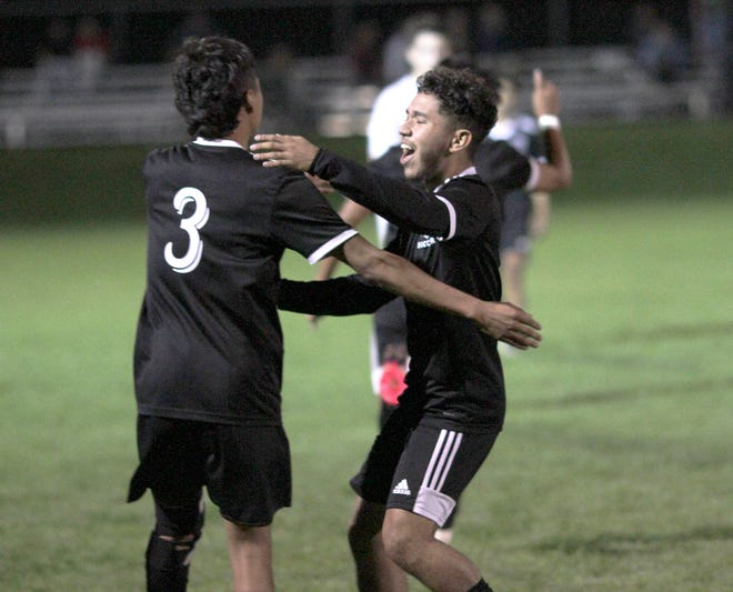 Fredy Camacho (5) and Alejandro Nieves (3) of Sturgis share a hug following the Trojans' come-from-behind win over Harper Creek in prep district soccer action on Wednesday.