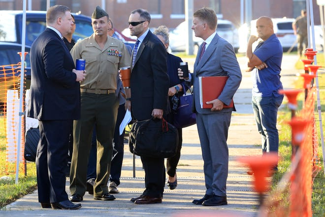 Lt. Col. Stuart SchellerJr. walks to the courtroom on Camp Lejeune in Jacksonville NC, surrounded by his legal team and family, on Thursday, Oct. 14, 2021. Scheller is being court-martialed following his public comments in August and September that criticized the American withdrawal from Afghanistan.