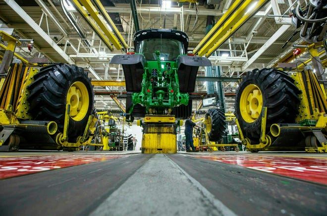 In this April 9, 2019, wheels are attach as workers assemble a tractor at John Deere's Waterloo, Iowa assembly plant. The vast majority of United Auto Workers union members rejected a contract offer from Deere & Co. Sunday, Oct. 10, 2021 that would have delivered at least 5% raises to the workers who make John Deere tractors and other equipment. (Zach Boyden-Holmes/Telegraph Herald via AP, File)